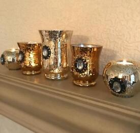 Brand new set of 5 gold glass candle holders.