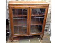 Wooden bookcase or display cabinet with two leaded glass doors and fixed wooden shelves.