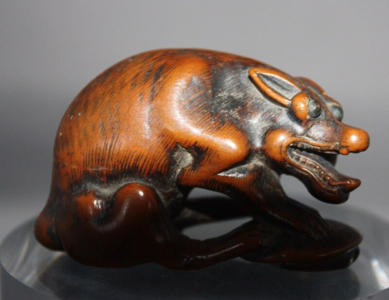 JAPANESE WOOD NETSUKE OF A WOLF HOLDING A TORTOISE, Mid-18th CENTURY AND SIGNED