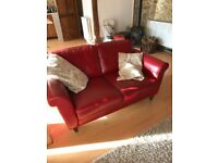 Two red leather effect sofas