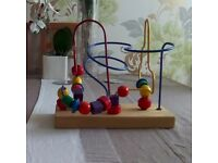 Toy with three curly wires with different shaped wooden shapes that can be moved round the wires.