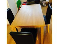 Wood dining table with 4 black leather chairs