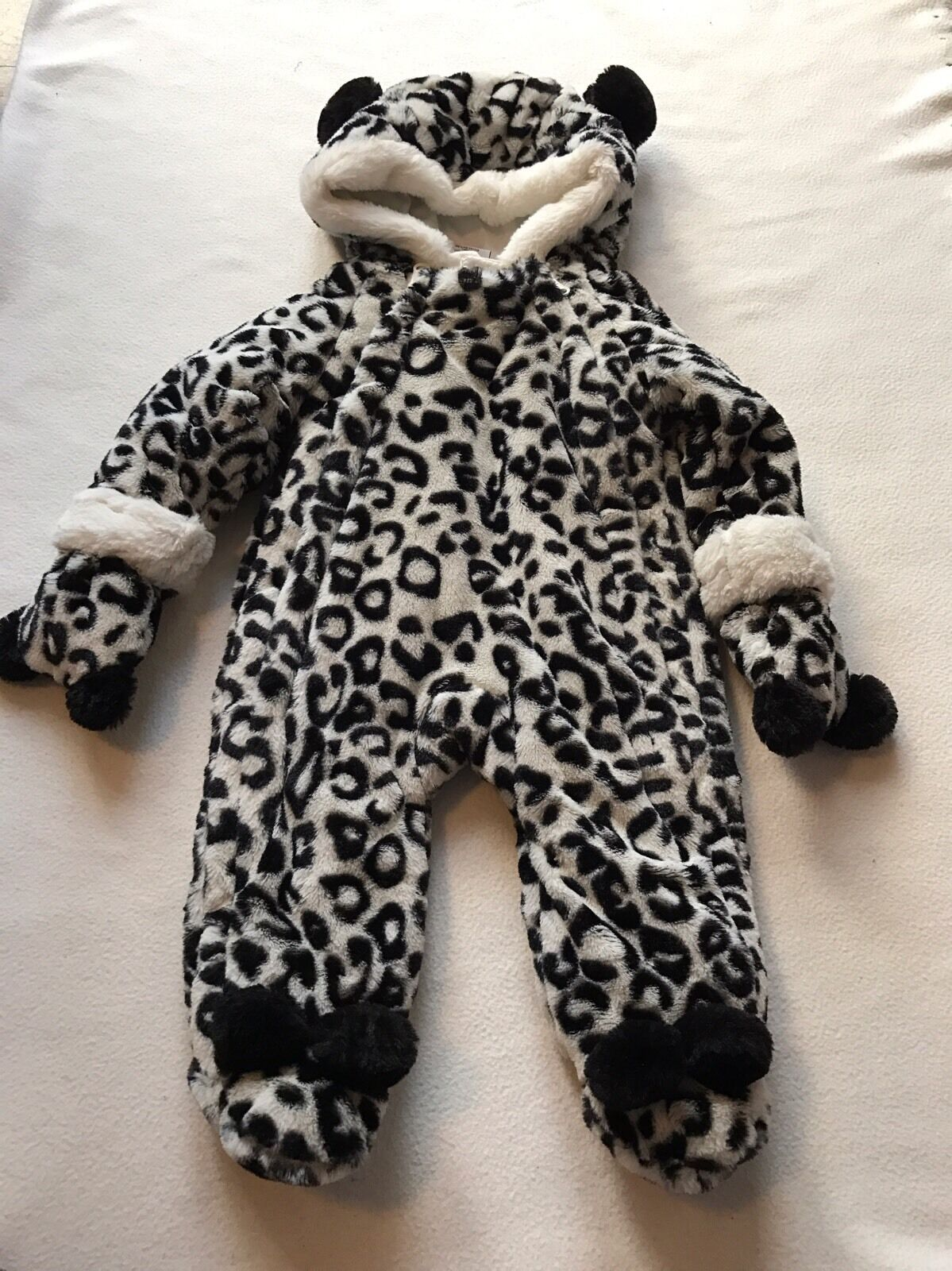 Cosy snowsuit in peony leopard print. Concealed zip closure through front with a removable hood and matching mittens. With concealed feet for sizes months.