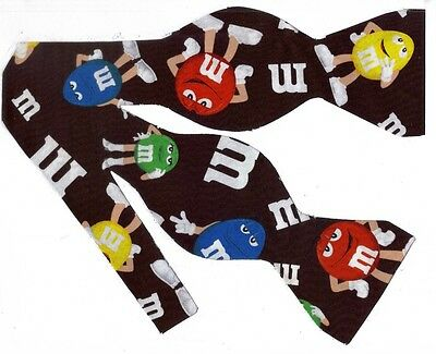 (1) SELF-TIE BOW TIE- M&M CANDY CHARACTERS ON A CHOCOLATE BROWN BACKGROUND