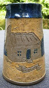 RARE PICHET EN GRES UMH BREIZH - France - Rare pichet en grs De forme conique, Il est décoré d'une chaumiere et d'arbustes incisés de couleur grise et bleue. L'anse et le haut du pichet sont bleus. Mention PENTI Dimensions: 20,8 cm diamtre la base : 12 cm, diamtre au plus large :14 cm - France