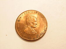 Small brass colored medal honoring President Lincoln / The Great Emancipator