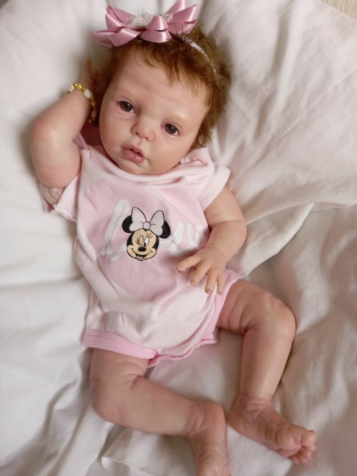 Reborn doll with beautiful rooted hair .