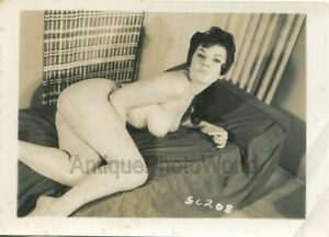 Sultry-brunette-nude-woman-posing-on-bed-vintage-pin-up-photo