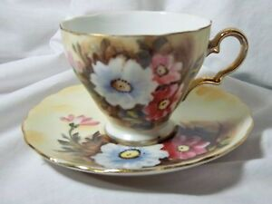 VINTAGE ENESCO  CUP AND SAUCER PURPLE WHITE FLOWERS GOLD TRIM #E1432