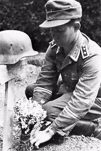 WW2-Adjudant-allemand-fleurissant-la-tombe-d-039-un-caporal-Normandie-aout-1944