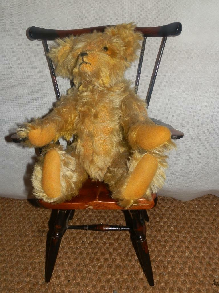 Osito de peluche anaranjado, con ojos de cristal y sillas de violín de madera.