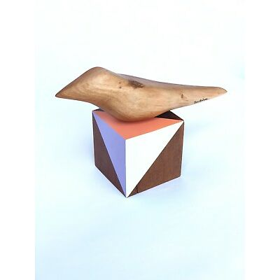 Hand carved bird standing in wood cube made from recycled wood
