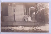 VINTAGE REAL PHOTO GIRL AND BABY ON HOUSE PORCH POSTCARD