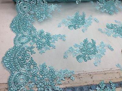 Aqua unique flower design embroider and corded on a mesh lace-prom-sold by yard.