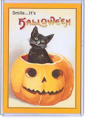 VINTAGE REPRODUCTION SMILE IT'S HALLOWEEN BLACK CAT IN PUMPKIN REPRO POSTCARD