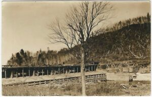 Pine-Forest-Logging-on-River-with-Bridge-amp-Building-Real-Photo-Postcard