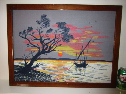 large vintage needlepoint art picture of a sailboat anchoring offshore in sunset