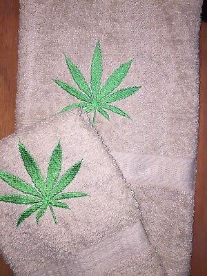 MARIJUANA LEAF DESIGN EMBROIDERED ONTO A DARK BROWN COLOR HAND TOWEL