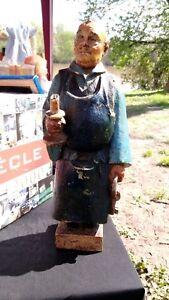 Statuette bois - France - Statuette représentant un homme , peut-tre un moine, portant une chandelle, et de l'autre main, un trousseau de clés.C'est peut-tre un personnage asiatique, car le visage et les mains sont plutot jaunes.Il y a une signature gravée sur le bas,  - France