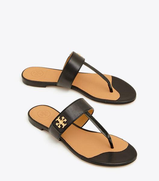 Las sandalias de toro Burch Kira, las zapatillas negras, el símbolo dorado.