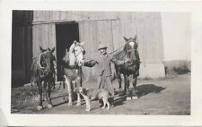 VINTAGE IMAGE OF A MAN OUTSIDE OF A BARN WITH THREE HORSES AND A DOG.