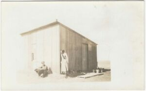 1910s-Woman-Peers-at-Man-Sitting-by-Tarpaper-Shed-Humor-Real-Photo-Postcard