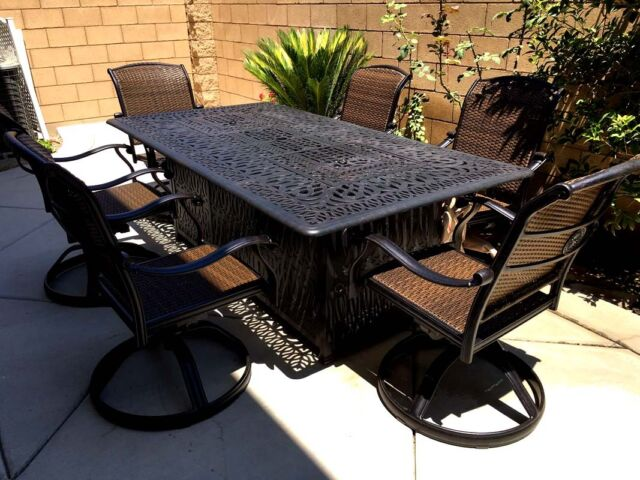 Outdoor dining table with fire pit 7 piece cast aluminum patio furniture.