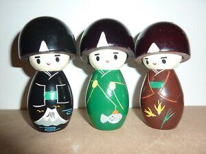 THREE JAPANESE 12 CM HIGH WOODEN GREEN,BLACK,BROWN PAINTED DESIGN KOKESHI DOLLS