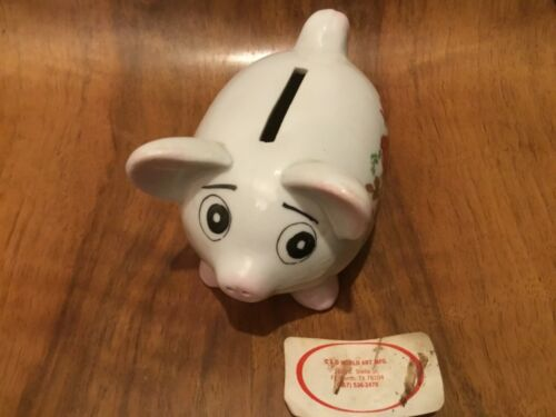 A charming medium sized piggy bank with floral decoration and a sheepish smile