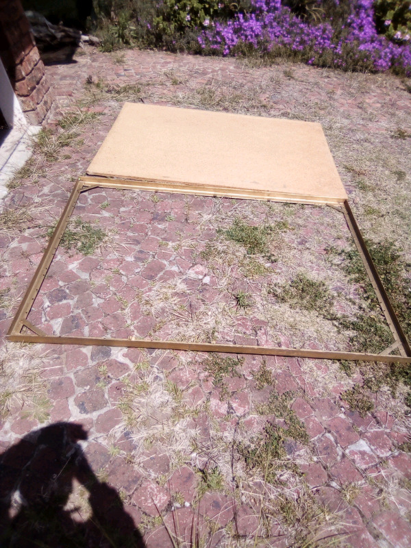 A flat steel support base (no legs) together with used chipboard base