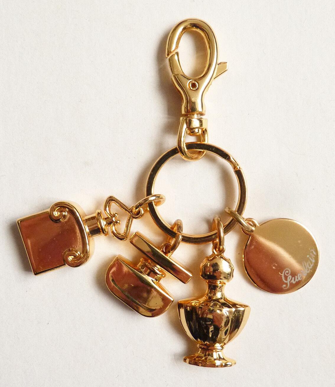 Porte clés GUERLAIN avec breloques en métal doré bijou