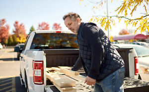 Man unloading wood from the bed of his pickup truck