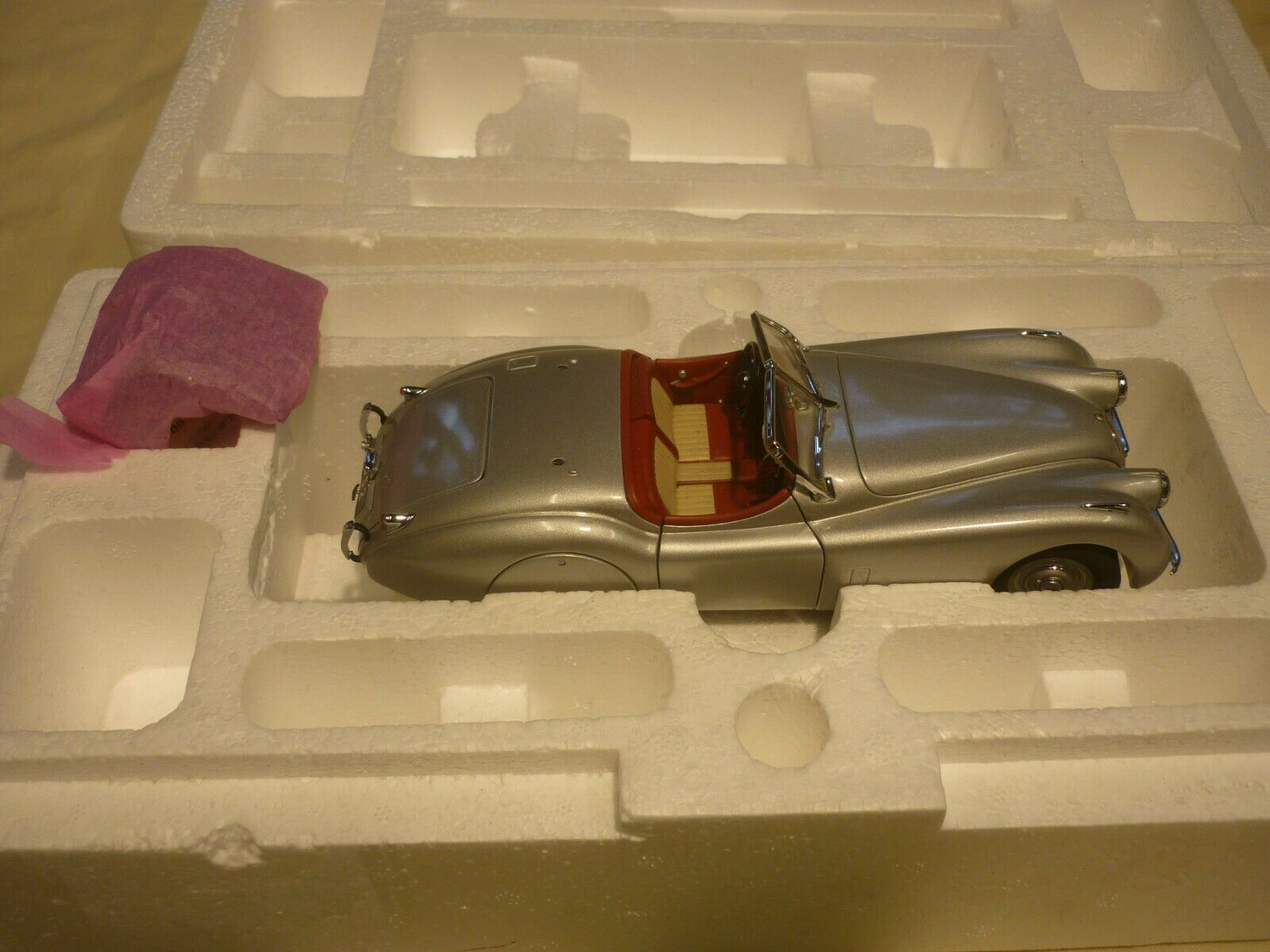 A franklin mint of a scale model of a 1952 jaguar XK120 with hood