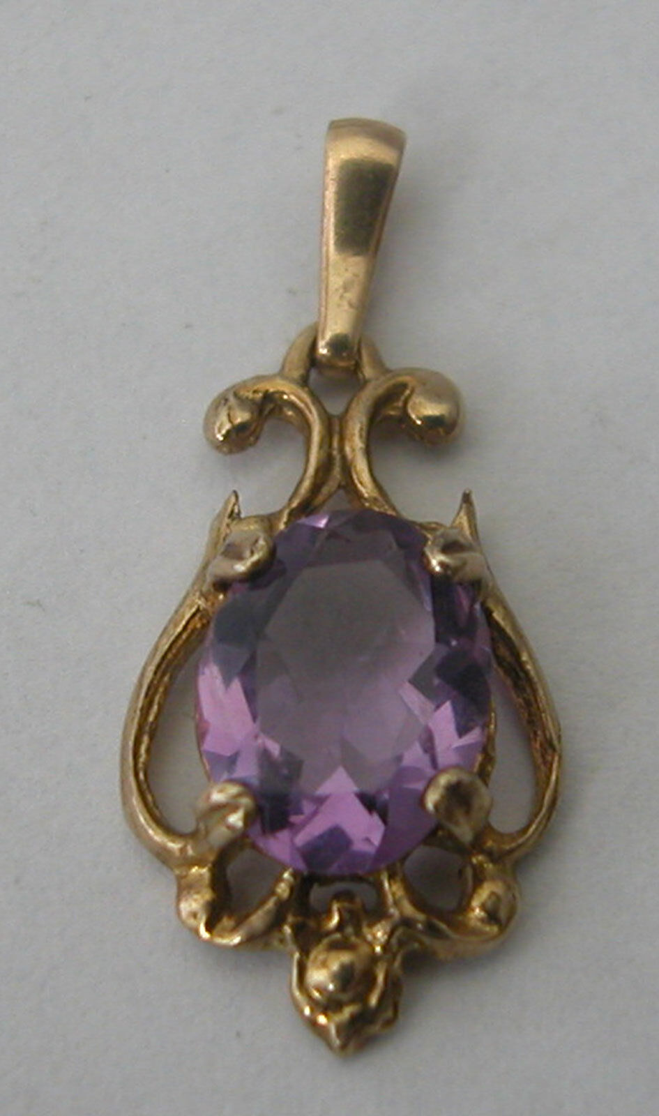A CUTE 9 K YELLOW gold PENDANT SET WITH AN OVAL FACETED AMETHYST OF 1 CARAT