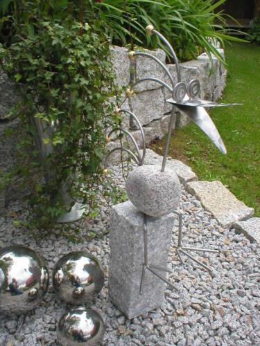 Vogel aus Granitstein und Edelstahl auf Granitsäule sitzend