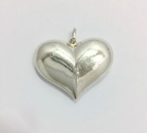 hollow form heart pendant with blue patina. Fine silver
