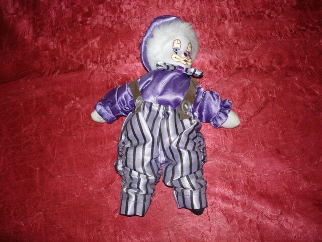Kleiner Clown, Porzellan-Kopf, Körper mit Sand gefüllt, lila gekleidet, mit Hose