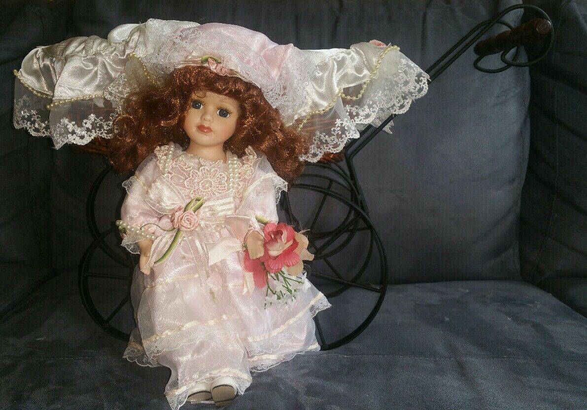 VINTAGE COLLECTIBLE PORCELAIN DOLL IN MUSICAL CARRIAGE