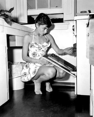 AUDREY HEPBURN OPENS OVEN DOOR IN KITCHEN WHILE IN BARE FEET 8X10 PHOTO FB-460