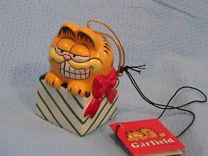 ENESCO GARFIELD CAT CHRISTMAS ORNAMENT sitting in a present with paper tag