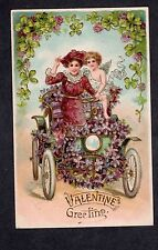 A157 Postcard Valentine woman driving with cupid embossed
