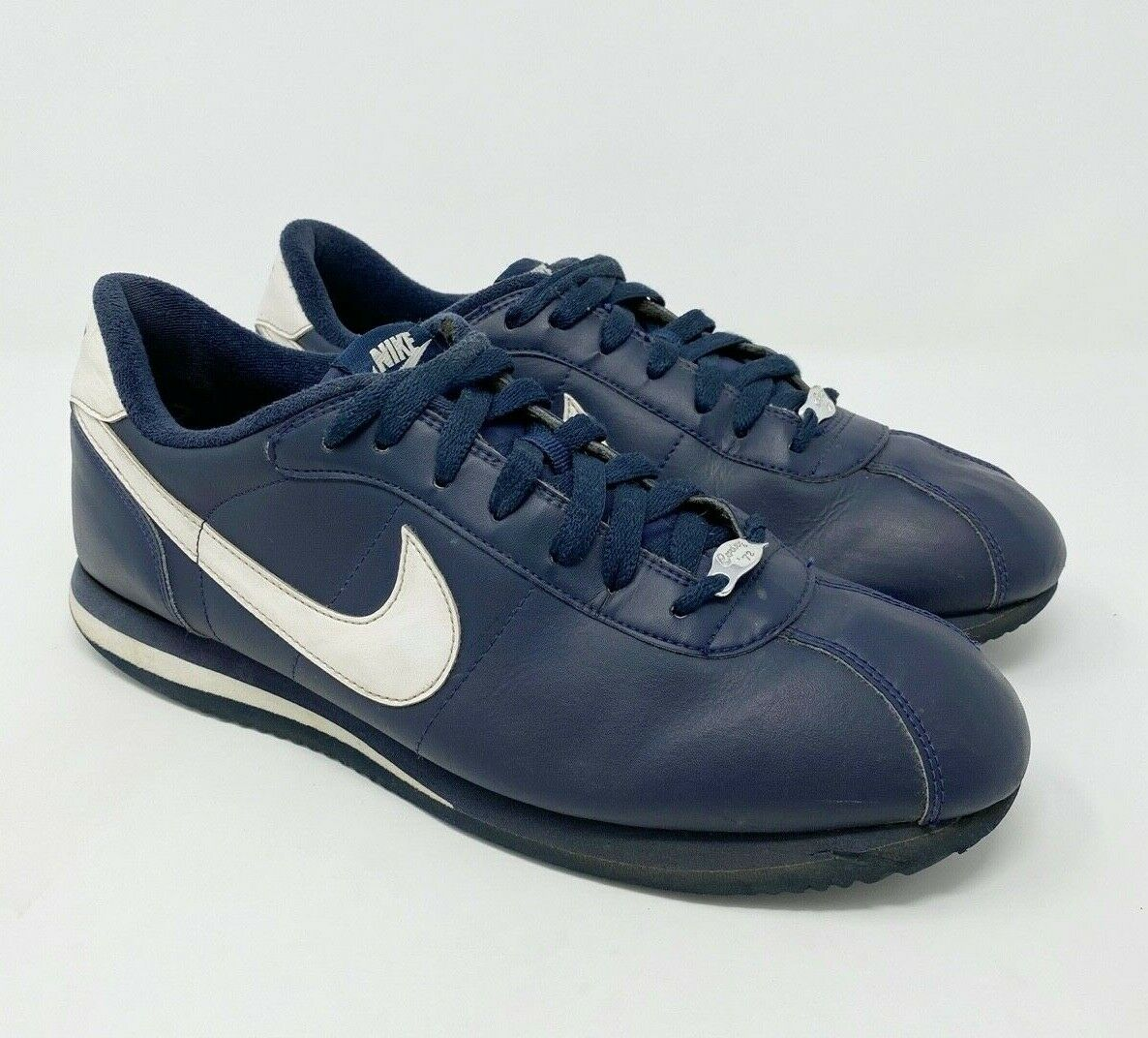 white and navy blue nike cortez
