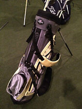 """US Kids 34"""" stand bag in black and yellow. 33"""" putter, 41"""" 3 wood."""