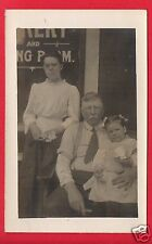 RPPC MAN WOMAN EYEGLASSES LITTLE GIRL ON LAP W/ PAPER BAG OF CANDY FROM DRUG CO.