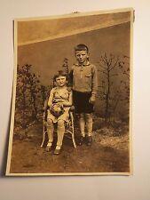 2 Kinder - Junge in kurzer Hose & Mädchen mit Ball auf einem Stuhl / Foto