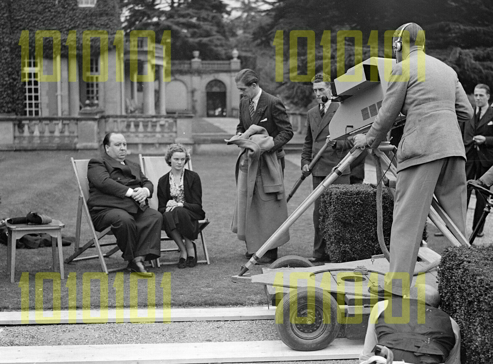 Alfred Hitchcock and Nova Pilbeam being interviewed by Leslie Mitchell (holding coat) in the gardens of Pinewood Studios on 5 October 1937 for Round the Film Studios BBC short