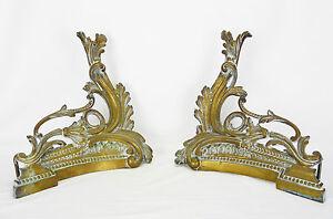 Ancienne paire de chenets rococo en bronze doré ACCESSORY fireplace cheminée - France - PAIRE DE CHENETS en bronze ciselé et doré décor de volutes rocailles symétriques . Les chenets ont conservé leurs fers d'origine. Dimensions (unité) : 35 cm x 35 cm x 12,5 cm Poids (unité) : 1,8 kg & 2,040 kg PAIR OF CHENETS gilt bronze sc - France