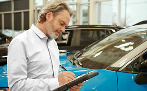 Man looking at clipboard in a car dealership