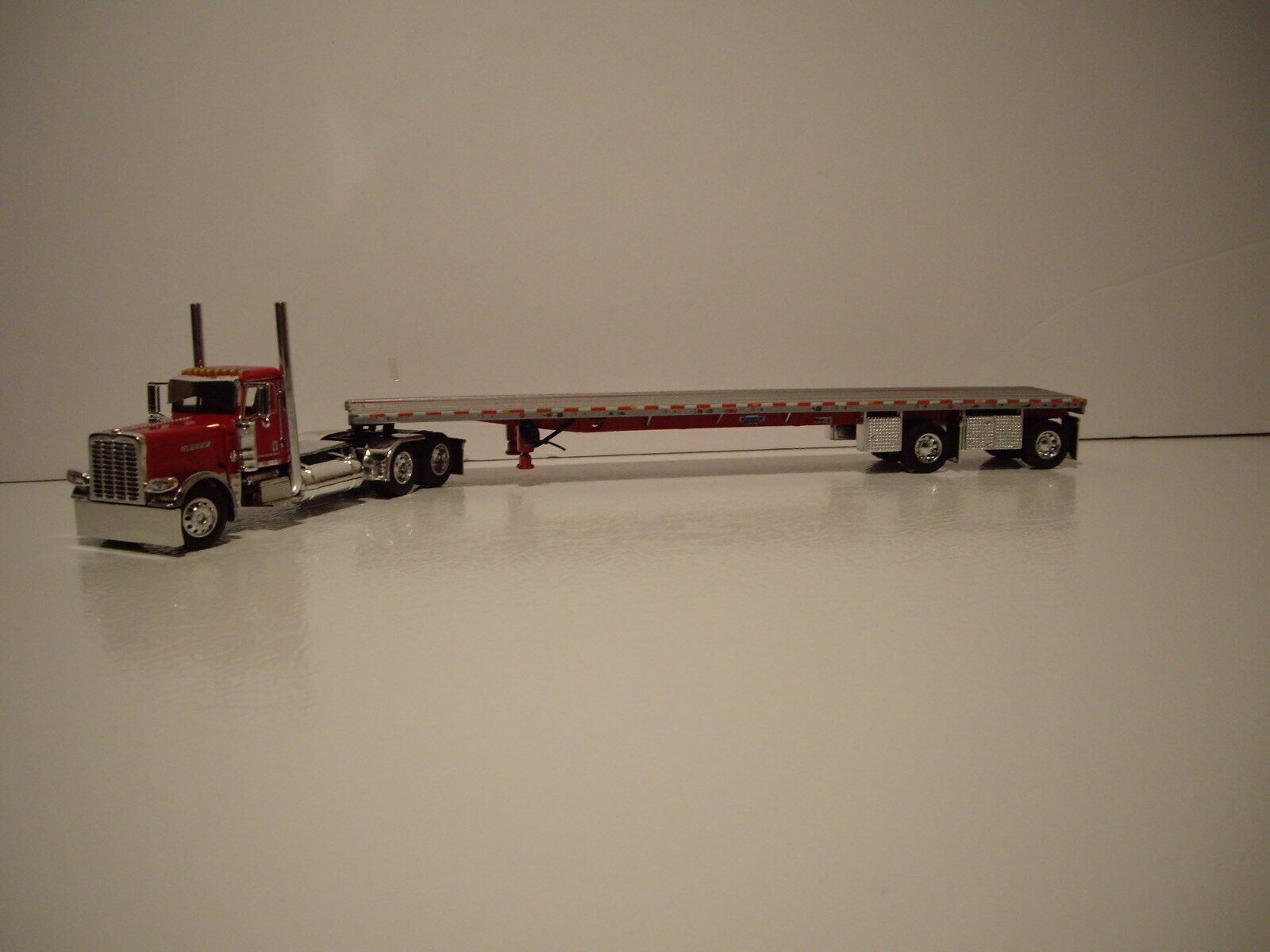 DCP FIRST GEAR 1 64 RED PETE 389 PRIDE N CLASS DAY CAB WITH SPREAD AXLE FLATBED
