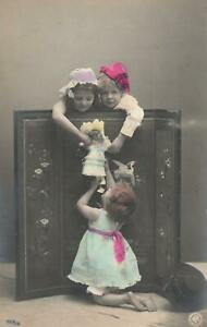 VINTAGE-REAL-PHOTO-of-3-CHILDREN-amp-GERMAN-PORCELAIN-DOLL-POSTCARD-UNUSED